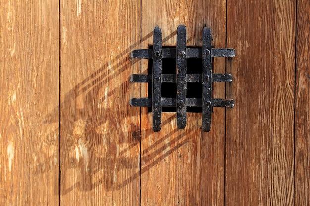 Porte en bois ancienne fenêtre grille en métal noir