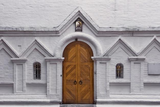 Porte en bois et deux fenêtres cintrées sur un mur de briques blanches. entrée de l'ancienne église chrétienne