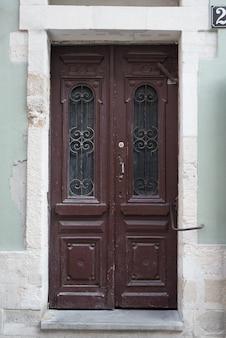 Porte en bois marron vintage avec éléments forgés.