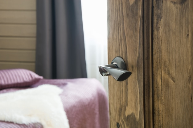 Porte en bois ouverte et vue sur la chambre et le lit. flou.
