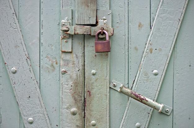 Porte en bois vert de l'ancien entrepôt, verrouillé avec cadenas