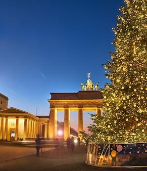Porte de brandebourg à berlin avec arbre de noël dans la nuit