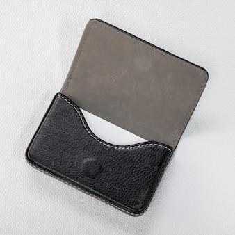 Porte-cartes en cuir noir et carte blanche sur fond blanc synthétique.