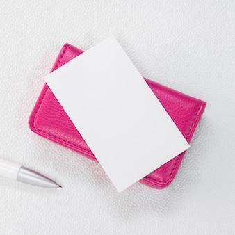 Porte-cartes en cuir rose et carte blanche sur fond blanc synthétique.