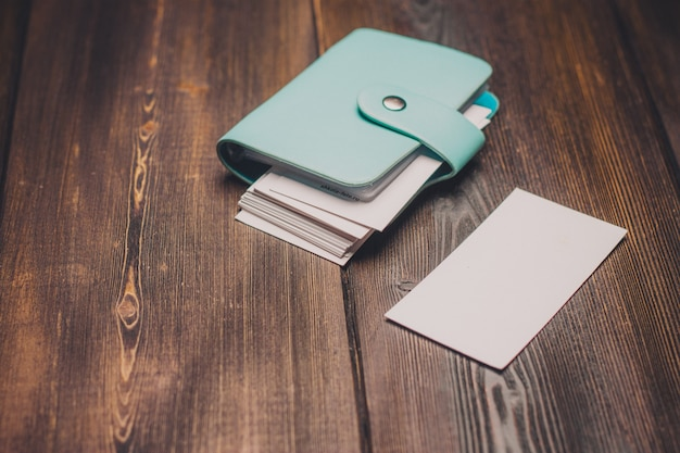 Porte-cartes de visite classique avec fermoir et table en bois en papier blanc. photo de haute qualité