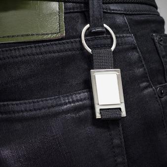 Porte-clés en acier suspendu à un jean noir.