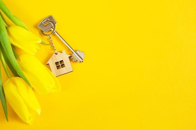 Porte-clés en forme de maison en bois avec clé sur fond jaune et tulipes au printemps.