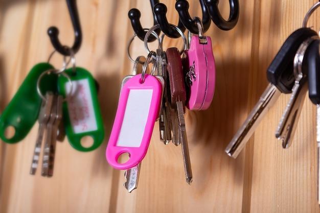 Porte-clés rose avec espace de copie et clés sur crochets dans le mur en bois du couloir comme toile de fond de nombreux autres porte-clés autour d'une faible profondeur de champ