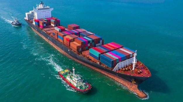 Porte-conteneurs arrivant dans le port, remorqueur et porte-conteneurs allant au port de haute mer, expédition et transport d'entreprise d'import-export logistique, vue aérienne.