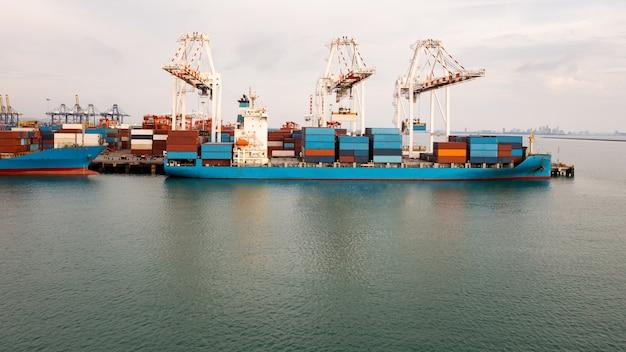 Porte-conteneurs au port industriel dans les services d'import-export mondiaux de logistique et de transport, chargement et déchargement de porte-conteneurs par grues, vue aérienne
