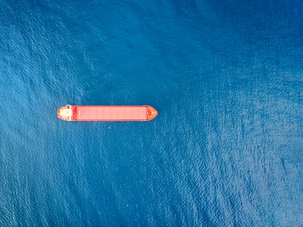 Porte-conteneurs de couleur rouge en mer tourné d'en haut. paysage aquatique pittoresque et bateau solitaire engagé dans des activités d'exportation et d'importation et de la logistique. expédition de marchandises. le transport de l'eau. vue aérienne de la mer et du bateau