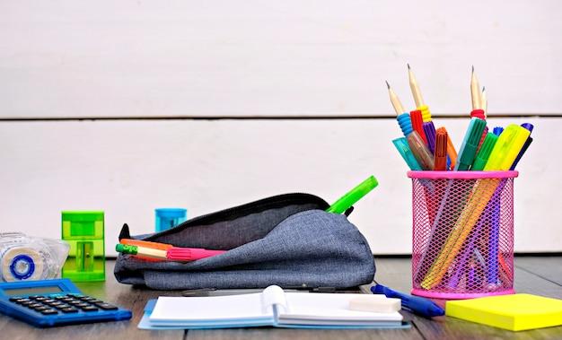 Porte-crayons et fournitures scolaires sur une table en bois