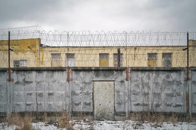 Porte dans le mur de la prison en béton avec du fil de fer barbelé