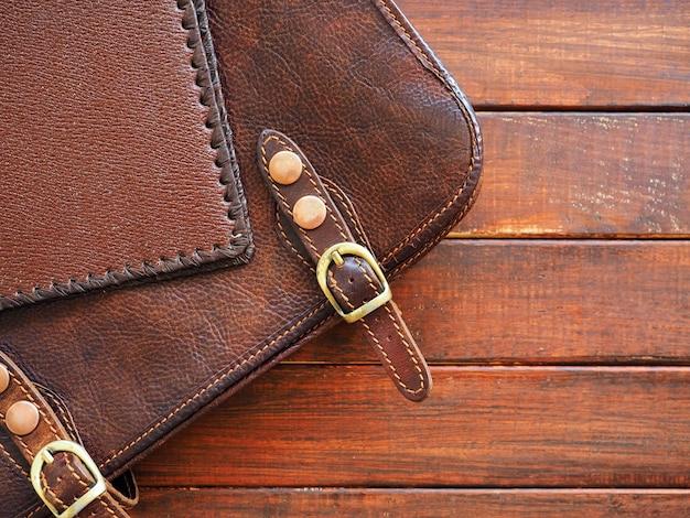 Porte-documents en cuir et note sur fond de bois libre