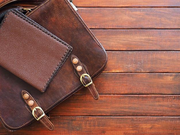 Porte-documents en cuir et note sur fond de bois