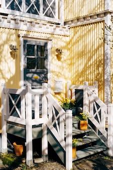 Une porte avec du verre dans un bâtiment en carton ondulé jaune avec des mains courantes blanches et des marches décorées avec