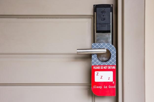 Porte fermée de la chambre d'hôtel avec s'il vous plaît ne pas déranger signe accrocher sur le bouton de porte