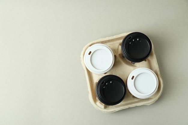 Porte-gobelet avec gobelets en papier sur fond gris clair