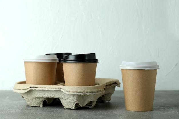 Porte-gobelet avec tasses à café sur table texturée grise