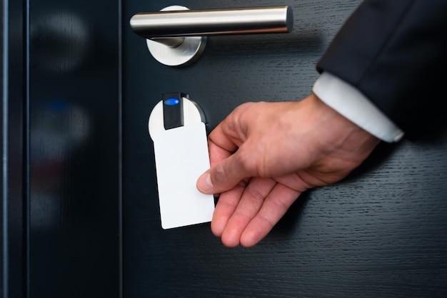 Porte de l'hôtel - jeune homme tenant une carte-clé en face du capteur électronique d'une porte de chambre