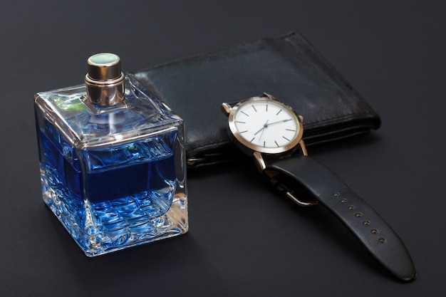 Porte-monnaie en cuir, montre avec un bracelet en cuir noir et eau de cologne pour homme sur fond noir. accessoires pour hommes. mise au point sélective sur la bouteille de parfum.