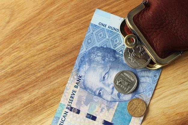 Porte-monnaie en cuir et un peu de monnaie et un billet de banque sur une surface en bois