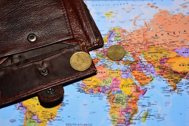Porte-monnaie ouvert avec deux centimes d'euros sur la carte du monde