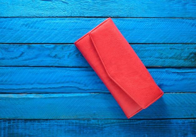 Porte-monnaie rouge à la mode sur un fond en bois bleu. vue de dessus. tendance du minimalisme.