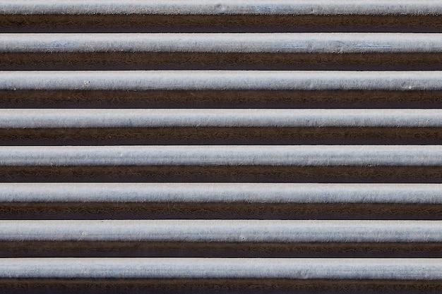 Porte d'obturation en métal, gris avec la rouille qui coule de l'humidité.