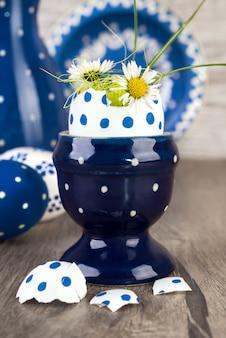 Porte-oeufs en céramique bleu avec fleurs dans un abri à oeufs, joyeuses pâques!