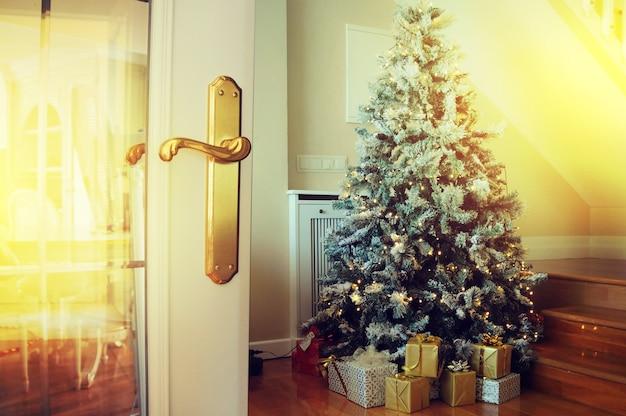 Porte ouverte et arbre de noël dans la chambre