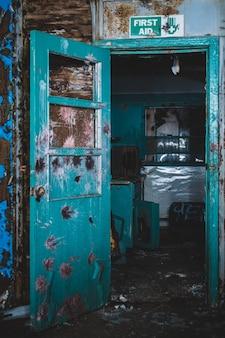 Porte ouverte bleue en bois dans une maison abandonnée