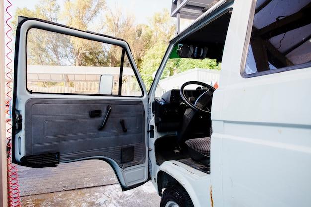 Porte ouverte d'une vieille camionnette blanche