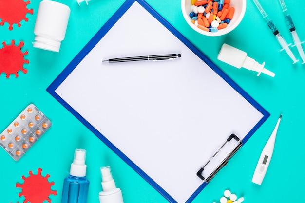 Porte-papier vue de dessus avec stylo, bactéries, sprays thermomètres et pilules sur fond bleu cyan. horizontal