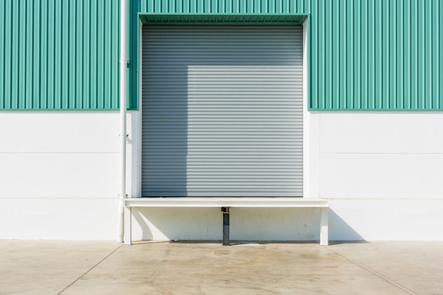 Porte à rideau et rampe de nivellement de quai à l'extérieur du bâtiment d'usine