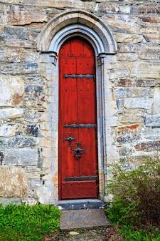 Porte rouge avec éléments en pierre sculptée dans le cadre