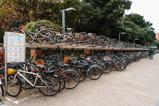Porte-vélos à deux étages le long du trottoir en face de l'université nationale de taiwan avec des gens qui marchent