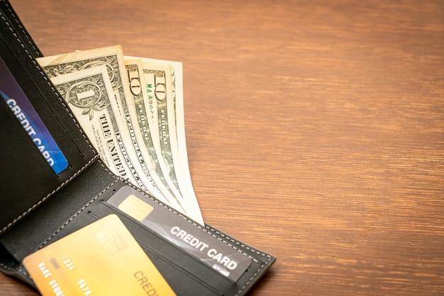 Portefeuille avec argent et carte de crédit - concept économie et finance