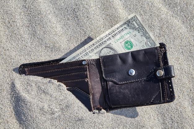 Portefeuille avec de l'argent dans le sable. concept de perte financière