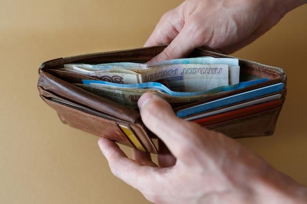 Portefeuille avec de l'argent entre les mains de l'homme