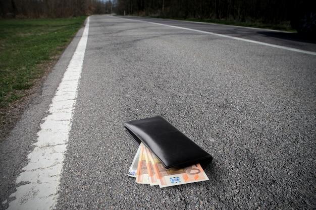 Portefeuille avec de l'argent sur la route