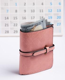 Portefeuille avec billets d'un dollar, calendrier de bureau sur fond blanc. shopping de vacances