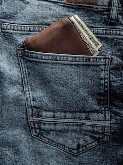 Portefeuille en cuir avec billets de cent dollars dans la poche arrière d'un jean bleu