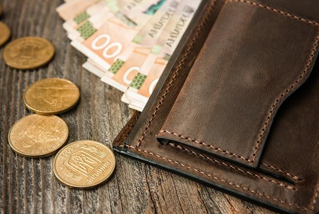Portefeuille en cuir marron avec des billets et des pièces de monnaie sur une vieille surface en bois. fermer.