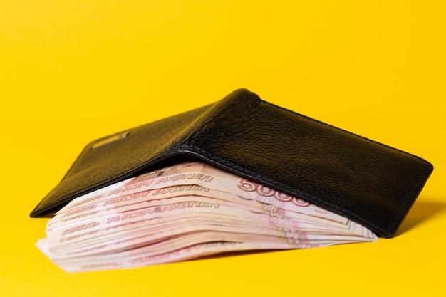 Un portefeuille en cuir noir est ouvert, rempli d'une pile de billets de cinq mille roubles.