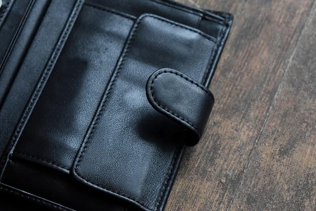 Portefeuille en cuir noir sur fond de bois clair