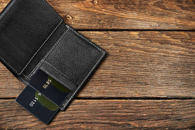 Portefeuille en cuir avec plusieurs cartes de crédit sur la table en bois.