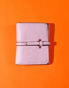 Portefeuille en cuir rose sur fond orange. vue de dessus