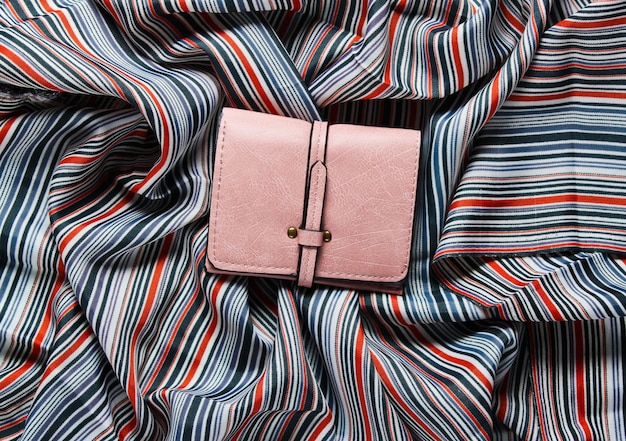 Portefeuille en cuir rose sur surface en tissu.