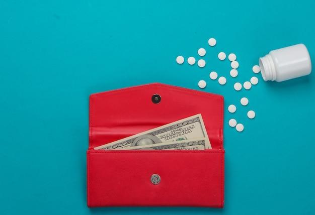 Portefeuille en cuir rouge avec billets de cent dollars, une bouteille de pilules sur un fond bleu.